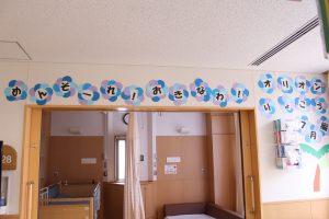「めんそーれ、おきなわ オリオンりょこう 7月編」と飾り付けている壁の写真