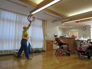 ピエロがフロアで輪投げの輪を持って立っている写真