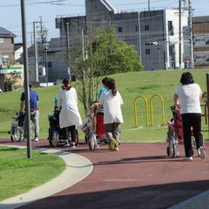 公園を職員に押されて車イスの利用者さんがお散歩している写真