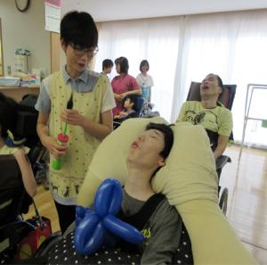 空気入れを持った職員とその横で車椅子に座った利用者さんの写真