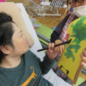 利用者さんがペンを持って絵に色を塗っている写真