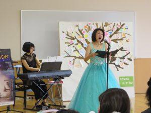 女性歌手がステージで歌う写真