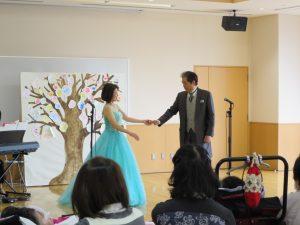 男性歌手と女性歌手が手を取りあって歌う写真