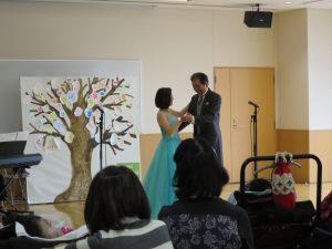 ステージで男性歌手と女性歌手が手を取りあって踊りながら歌う写真
