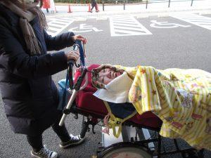 利用者さんと車椅子に手をかけるスタッフの写真