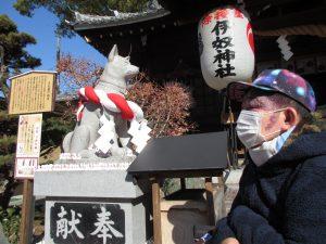 神社の犬の像の横に並ぶ利用者さんの写真
