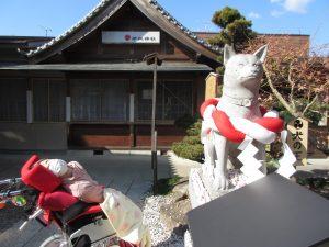 神社の犬の像の後ろにいる利用者さんの写真