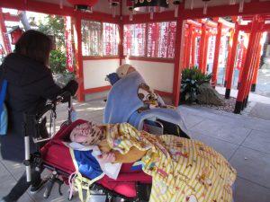 神社の鳥居をバックにして帰りの準備支度をする利用者さんとスタッフの写真