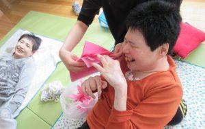 利用者さんが花紙を持って笑顔でいる写真