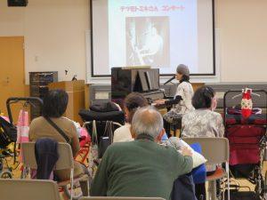 利用者さんが集まりピアノを弾いている女性の歌を聴いている写真
