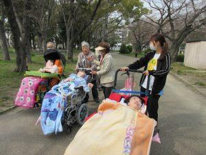 公園の道を車いすに乗る利用者さんをスタッフと保護者さんが押して歩く写真