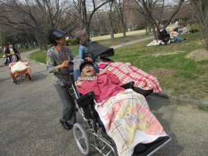 保護者さんが公園の道を車椅子の利用者さんを押して歩く写真