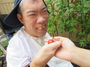 利用者さんが手にミニトマトを持って笑顔でみえる写真