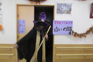 紫の帽子をかぶり、黒い装束にほうきを持った占い師の姿