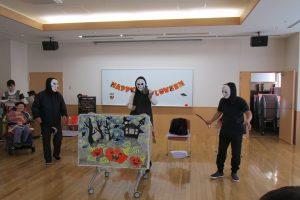 黒い服をして白いお面をかぶったお化けが3人で劇の舞台に登場している様子