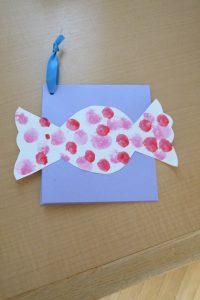 キャンディの形の白いカードに赤やピンクで水玉模様がつけられている様子