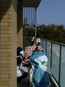 利用者さんと職員がベランダで日光浴をしている様子