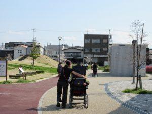 公園の小道を車イスに乗る利用者さんと職員が歩いている様子