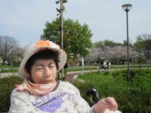 公園の桜をバックにした利用者さんのアップの写真