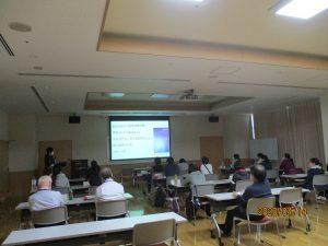 大きな部屋に数人の職員が座って講義を聴いている情景
