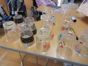 机の上にたくさんのプラコップが飾りつけされて並べてある様子