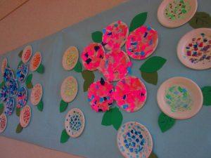 壁紙にピンクやむらさきの折り紙で作ったあじさいが貼ってある様子