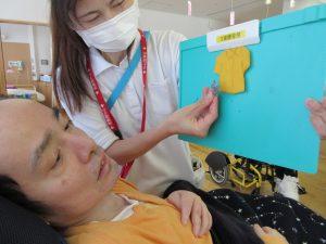 スタッフと利用者さんが小さな黄色のフェルトで作ったシャツを一緒に見ている写真