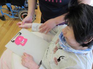 利用者さんがピンクのフェルトで作ったシャツをながめている様子
