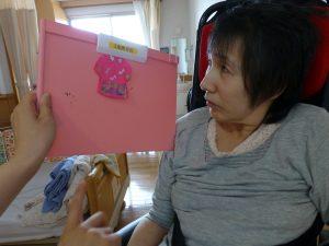 利用者さんとピンクのフェルトで作ったシャツと一緒に写っている写真