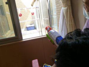 窓の外にある赤色の的をめがけて水鉄砲を発射している様子