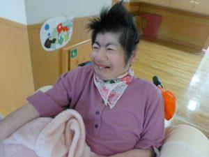 笑顔で車椅子に座っている女性の利用者さんの様子
