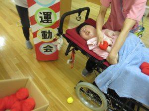 車椅子に寝ている利用者さんの手に赤い玉をもたせてあげている様子