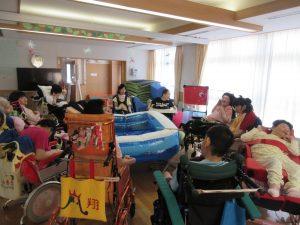 広いデイルームに車椅子に乗った利用者さん数名が集まっている様子