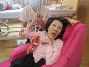 車椅子に乗った女性の利用者さんの横に赤い魚を釣ったスタッフがいる様子