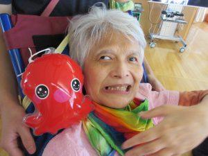 女性の利用者さんのお顔とその横に赤いタコのおもちゃが写っている様子