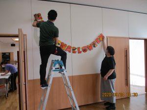 二人の事務スタッフが壁に飾りつけを行っている様子