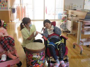車椅子に乗っている利用者さんが太鼓をたたけるように隣でスタッフが手伝いをしている様子