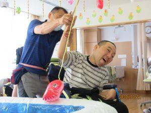 車椅子に乗った男性の利用者さんが嬉しそうな表情で棒の竿で赤い魚のおもちゃを釣っているところを、後ろに立つスタッフが手伝っている様子