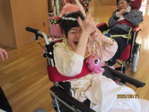 車椅子に乗った女性の利用者さんがピンクの魚のおもちゃを棒の竿で釣りながら笑顔でいる様子