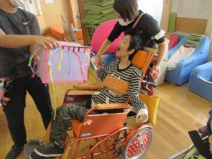 車椅子に乗った利用者さんが色とりどりの紐の中から紐を選んでいる様子