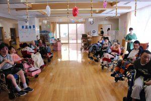 病棟のホールの両端に車椅子の利用者さんが数人ずつ並んでいる様子