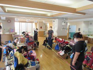 車椅子に乗った利用者さんたちが左右に並んでおり、その真ん中に長い色の紐を伸ばして立っているスタッフがいる様子