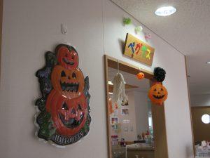 壁にオレンジのハロウィンの飾りがたくさん飾ってある様子