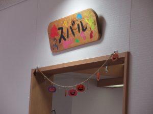 スバルの看板の下にオレンジのかぼちゃの飾りがぶら下がっている様子