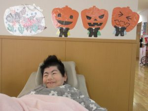 利用者さんのあたまの上の壁にオレンジのかぼちゃの飾りが並んで貼ってある様子