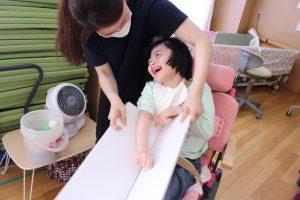 女性の利用者さんがスタッフの手を借りて玉入れの玉を取る練習をしながら笑っている様子