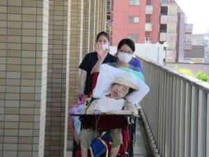 車椅子に座った利用者さんをスタッフが押して散歩している様子