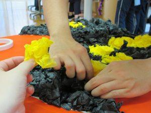 複数の手が丸めた黒い花紙と黄色の花紙を貼り付けている様子