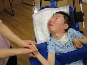 車椅子に乗った利用者さんがスタッフと一緒に手を握りながら紙を持っている様子