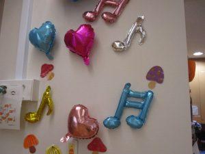 壁に色とりどりのハートや音符の飾りつけがしてある様子